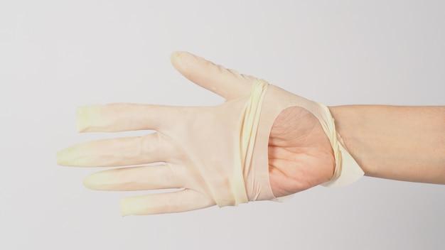 흰색 배경에 찢어진 의료용 장갑이나 찢어진 고무 장갑을 끼고 손을 클로즈업하세요.