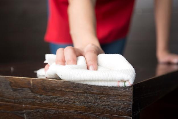흰색 냅킨으로 나무 테이블을 닦아 손 클로즈업