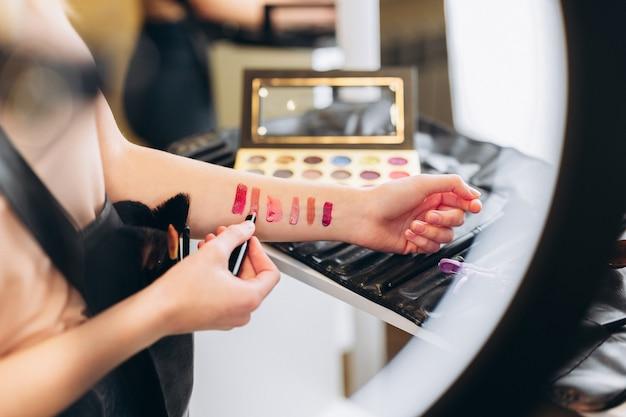 口紅または光沢見本による手のクローズアップ。手には赤とピンクの口紅とキラキラが描かれています。口紅またはリップグロスの色の選択。