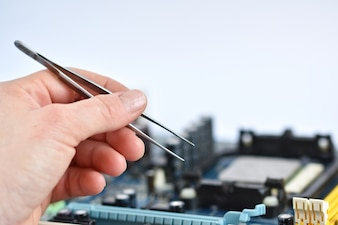 Close-up of hand with pliers to check a motherboard