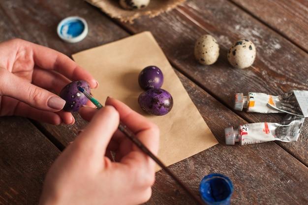 卵を着色する手のクローズアップ。