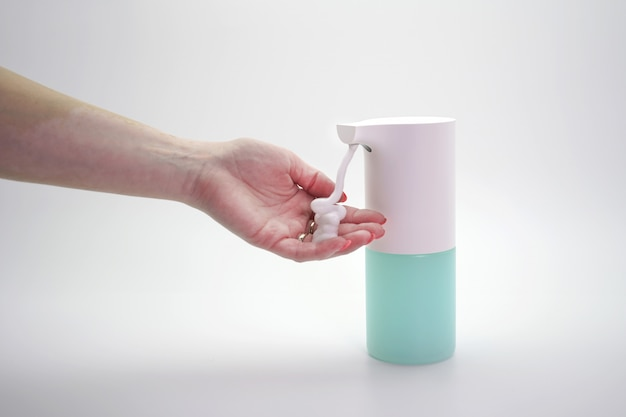 Конец-вверх рук продезинфицированных с автоматическим распределителем пены, изолированная стена. защита от вирусов и бактерий