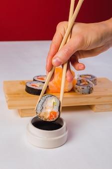 箸で寿司を食べる手のクローズアップ。