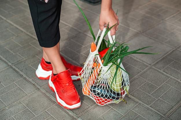 유기농 야채와 함께 가방을 잡는 손 클로즈업
