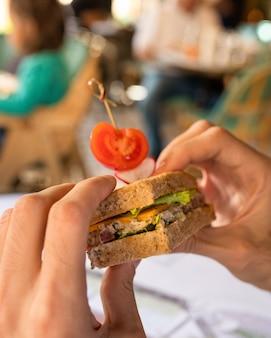 サンドイッチを持っている手のクローズアップ