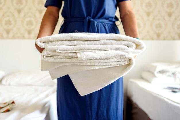 新鮮な白いバスタオルのスタックを保持している手のクローズアップ。ホテルの部屋のクライアント。