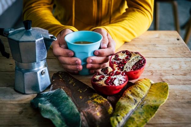暖かいvcoffeカップを持っている手のクローズアップ-健康的なバイオの概念km0食品栄養のライフスタイルと人々-秋の気分-木製のテーブル-モカカフェイタリアンドリンク