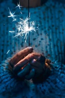 花火線香花火を持っている手のクローズアップ-青い冷たいトーン-感情と感情の概念の人々-希望と愛のイメージ