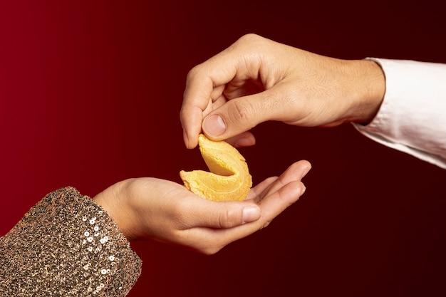 Конец-вверх рук держа печенье с предсказанием на китайский новый год