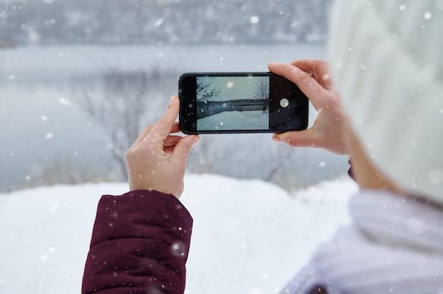 Крупным планом руки держат смартфон и снимают природу во время падающего снега