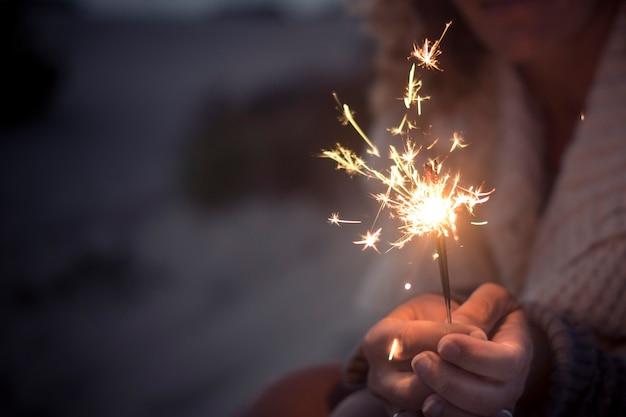 新年のお祝いに線香花火の光を保持している手のクローズアップ