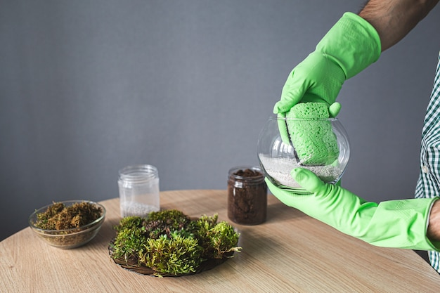 Крупным планом руки в перчатках протирают флорариум губкой. подготовка к пересадке комнатных растений.
