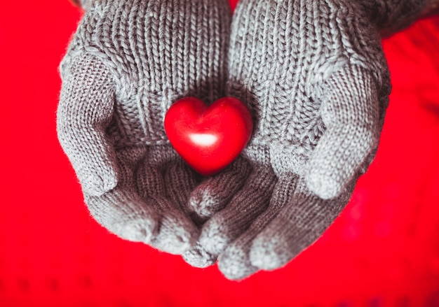 Крупный план рук в серых вязаных варежках с красным сердцем