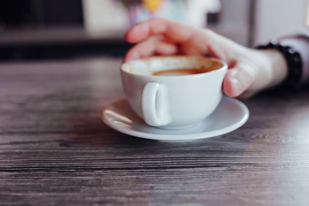 커피와 함께 손 남자의 닫습니다. 테이블에 커피 한 잔을 들고 남자 손.