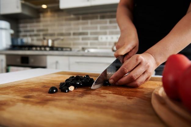 木の板にブラックオリーブを刻んでいる女性の手のクローズアップ。食品の準備の概念
