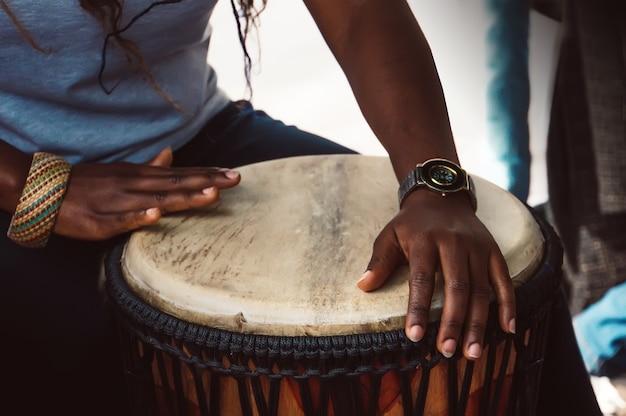 드럼을 연주하는 여자의 손을 닫습니다.