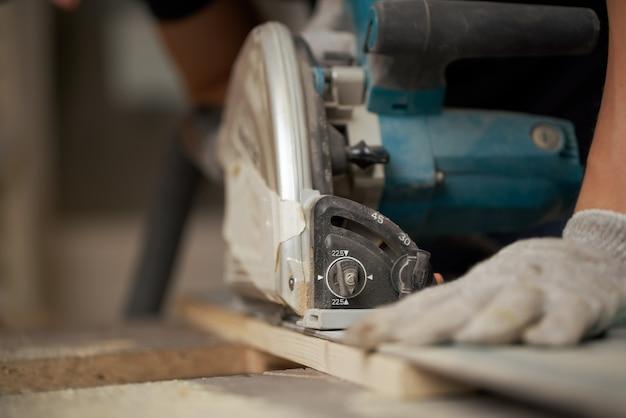 퍼즐로 나무 판자를 톱질하는 목수의 손 클로즈업