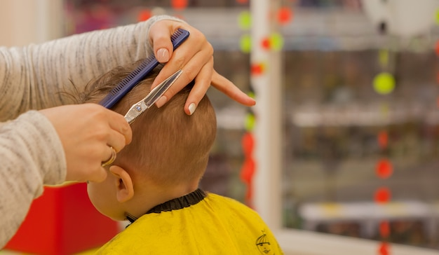 美容師の手のクローズアップ。女性は立って、小さな男の子のために散髪をしています。彼女は櫛とはさみを持っています