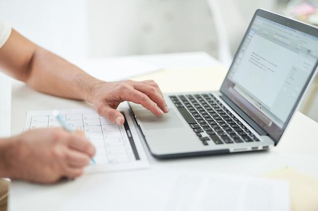 노트북을 사용하고 데스크탑에서 작업하는 동안 달력에 날짜를 표시하는 남자의 손을 닫습니다. 온라인으로 일하고 집에서 공부하는 개념