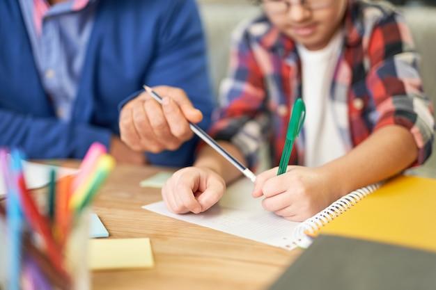 自宅の机に一緒に座っている間、彼の息子、学童の宿題を手伝っている中年のラテン系の父の手のクローズアップ。遠隔教育、家族、父性の概念