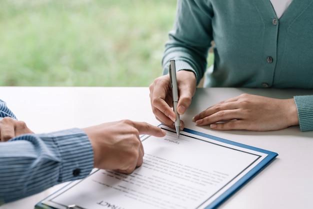 Крупный план рук агента по недвижимости и клиента, подписывающего договор о покупке и продаже дома в офисе.