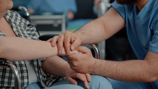 高齢の障害のある女性と男性の看護師の手のクローズアップ