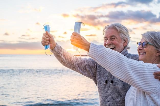 코로나바이러스에 승리한 후 손에 코비드나 바이러스를 보호하기 위해 마스크로 서로를 잡고 있는 두 사람의 손을 닫고 해변에서 야외에서 자유롭게 지내세요