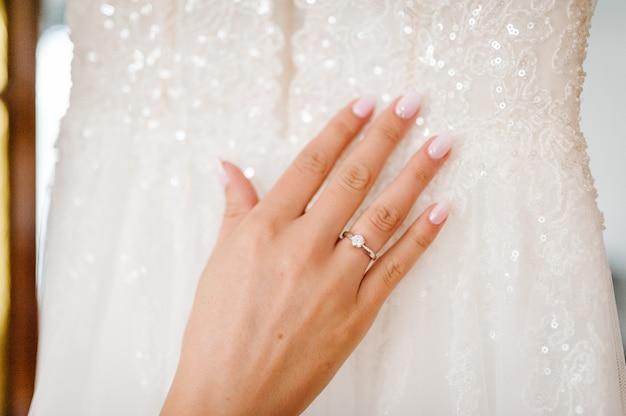 Закройте руки женщины, показывая элегантное кольцо с бриллиантом на концепции пальца, любви и свадьбы. обручальное кольцо на пальце невесты. день свадьбы. мягкий и выборочный фокус.