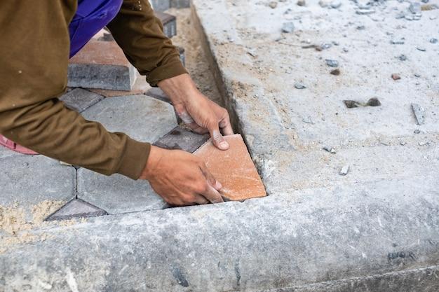 歩道の石ブロックを配置する作業をしている労働者の手のクローズアップ。