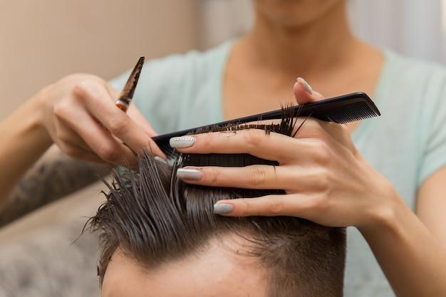 理髪店で魅力的な男性に散髪を作る若い理容室の手のクローズアップ。
