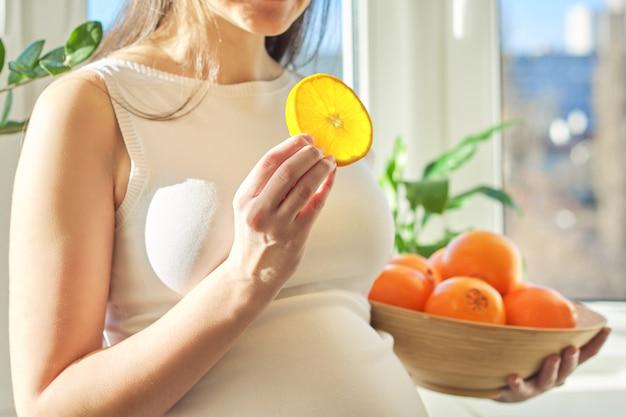 ボウルにオレンジを保持している若い妊婦の手のクローズアップ