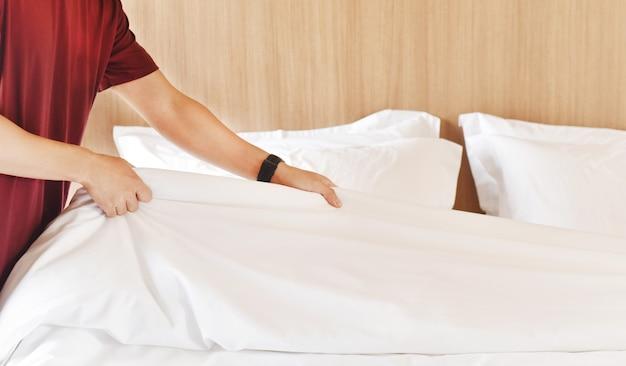 Крупный план рук, устанавливающих простыню. услуги горничной, уборка гостиничного номера.