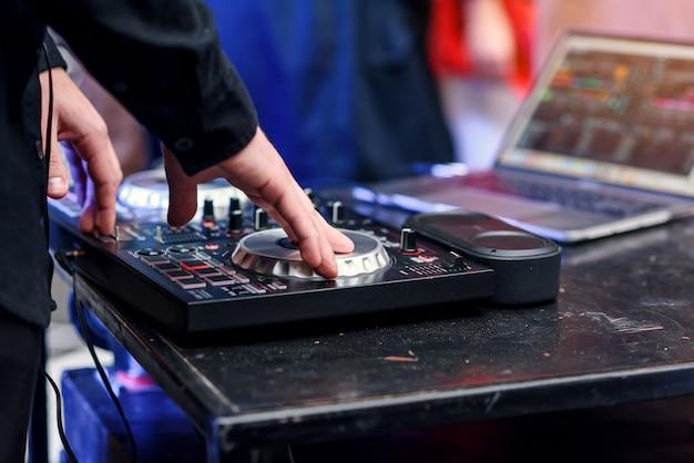Крупным планом руки вращаются палубы в ночном клубе