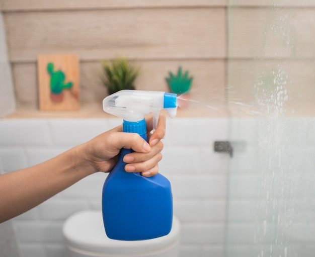Крупным планом руки распыляют распылитель для бутылок при мытье стекла в ванной комнате