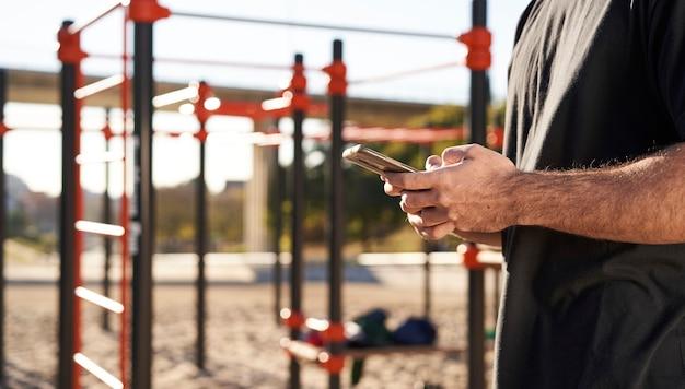 屋外の体操トレーニング中に、バーベルパークで彼のスマートフォンを使用して手のクローズアップ。