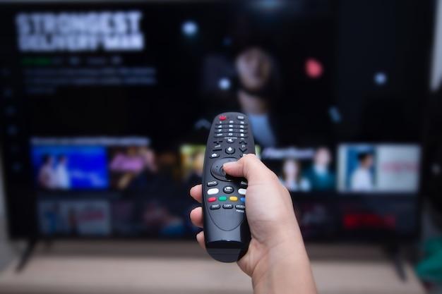 ビデオオンデマンドのぼやけたスマートテレビでリモートスマートテレビを使用している手のクローズアップ