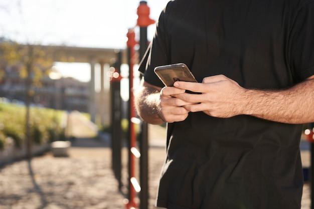 屋外の体操トレーニング中にスマートフォンを使用して手のクローズアップ。背景にはバーパークがあります。