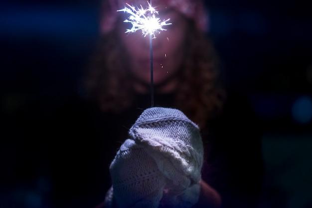 祝うために線香花火の光を保持している手袋で手のクローズアップ
