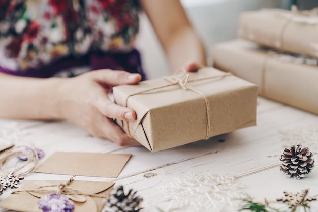 クリスマス装飾付きの木製テーブルの上の手の女性プレゼントギフトボックスのクローズアップ。