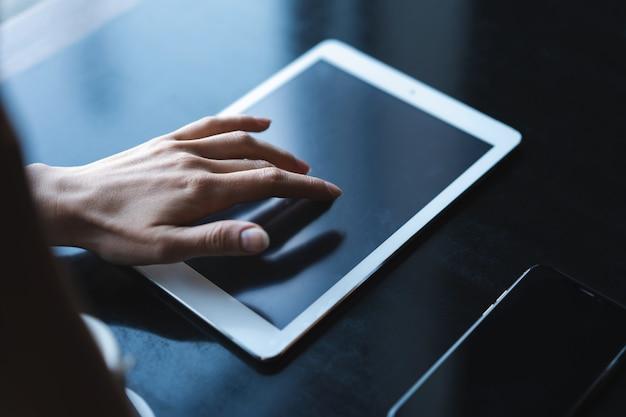 Закройте руки женщины, используя ее планшетный пк в ресторане, кафе.
