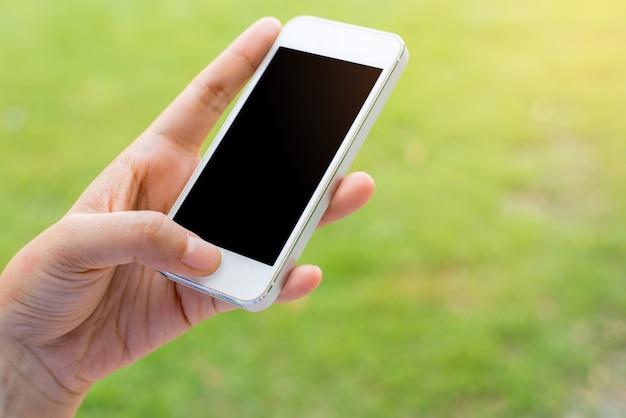 市内のスマートフォンを使用して手の女性のクローズアップ
