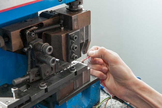 端子コネクタ付きケーブルを組み立てるために機械の後ろで作業している手のクローズアップ