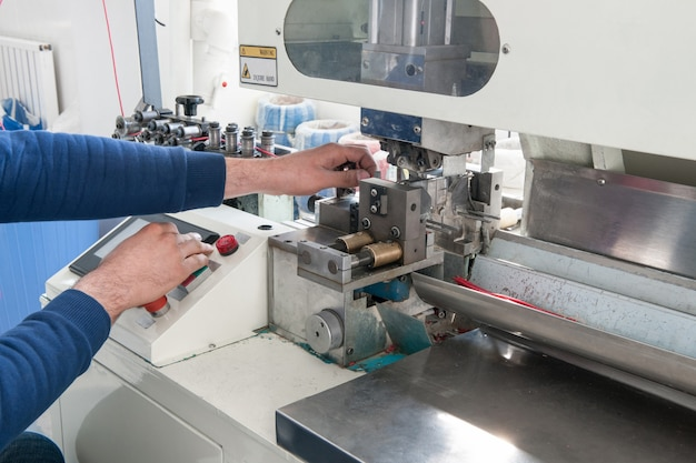 ケーブルを切断するための産業機械で作業している手のクローズアップ