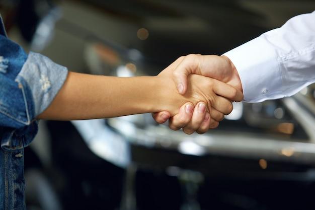 新しい車を買うために取引をした人々の握手のクローズアップ