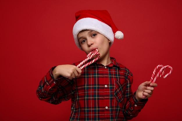 Крупный план красивого очаровательного мальчика в клетчатой рубашке и шляпе санта-клауса, дегустирующего сладкие сладкие рождественские леденцы, полосатые леденцы, смотрит в камеру, позирует на цветном фоне с копией пространства
