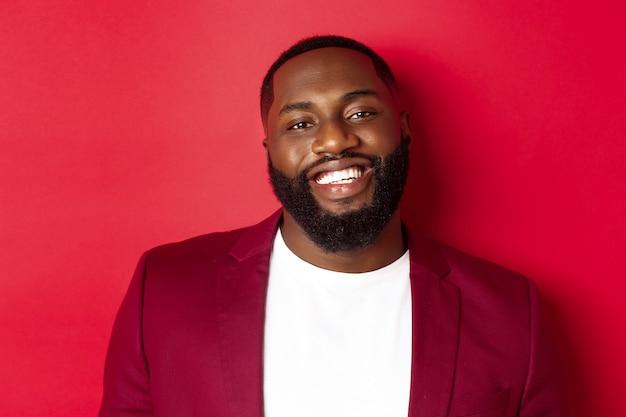 Крупный план красивого бородатого темнокожего мужчины, празднующего новый год, в праздничном наряде и счастливого улыбающегося человека, стоящего на красном фоне.