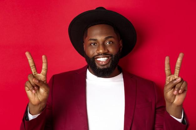 ピースサインを示し、幸せな笑顔のハンサムなひげを生やした黒人男性のクローズアップ