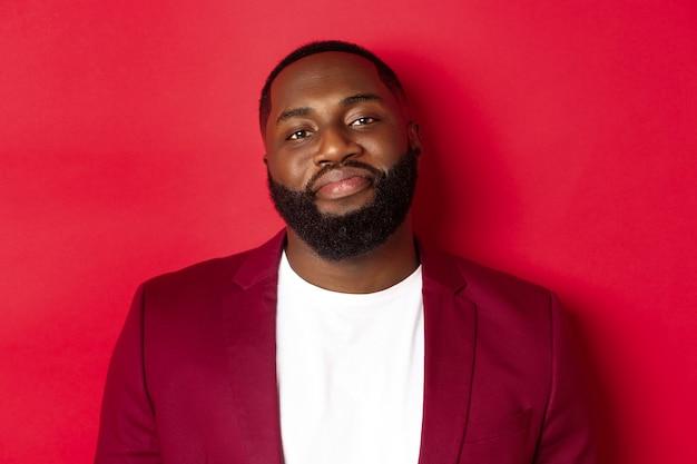 カメラの恥ずかしがり屋に微笑んで、tシャツのスタイリッシュなブレザーに立って、赤い背景の上に立っているハンサムなひげを生やしたふっくらした男のクローズアップ