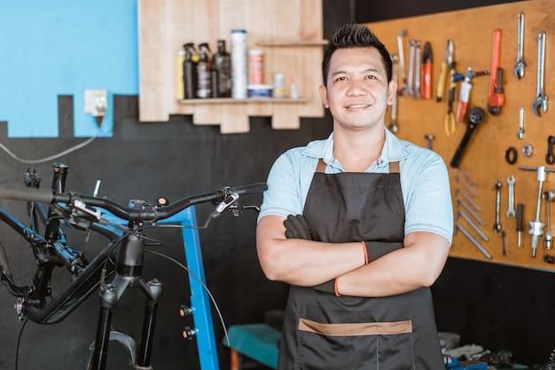 교차 손으로 자전거를 들고 웃는 앞치마에 잘 생긴 자전거 정비사의 클로즈업