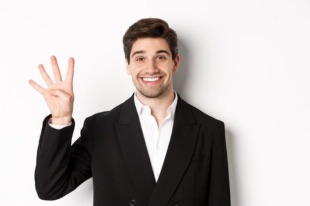 Крупный план красивого бизнесмена в черном костюме, изумленно улыбаясь, показывая номер четыре, стоя на белом фоне